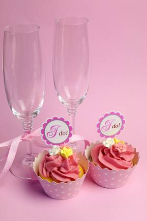 Pink wedding cupcakes with I Do topper signs - with champagne glasses and polka dot ribbon. photo