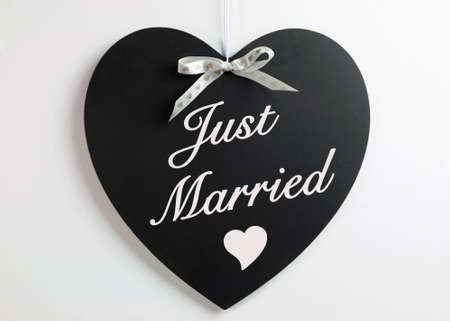 honeymoons: Heart shape blackboard with white hearts ribbon against a white background with Just Married message for weddings or honeymoons.