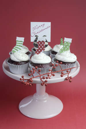 christmas tea: Christmas decorated chocolate red velvet cupcakes with white frosting and red and green festive decorations on pink cake stand and Merry Christmas message sign, against a red background. Verticak. Stock Photo
