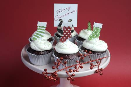 Christmas decorated chocolate red velvet cupcakes with white frosting and red and green festive decorations on pink cake stand and Merry Christmas message sign, against a red background. photo