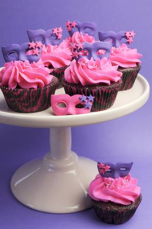 masquerade masks: Pink and purple masquerade masks decorated party cupcakes with pink frosting for teenage, birthday, New Years Eve, or wedding bridal shower party - vertical. Stock Photo