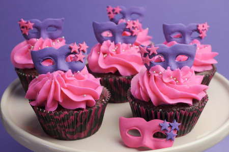 masquerade masks: Pink and purple masquerade masks decorated party cupcakes with pink frosting for teenage, birthday, New Years Eve, or wedding bridal shower party - close up. Stock Photo