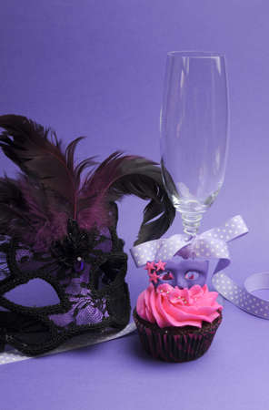 masquerade masks: Pink and purple masquerade masks decorated party cupcake with pink frosting for teenage, birthday, New Years Eve, or wedding bridal shower party - with champagne glass and mask, vertical.