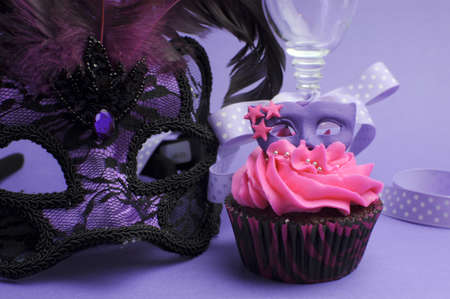 Pink and purple masquerade masks decorated party cupcake with pink frosting for teenage, birthday, New Years Eve, or wedding bridal shower party, with mask and champagne glass - close up. photo