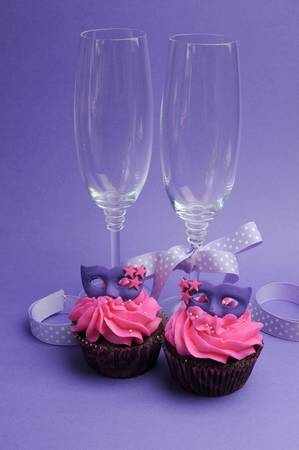 red velvet cupcake: Pink and purple masquerade masks decorated party cupcakes with pink frosting for teenage, birthday, New Years Eve, or wedding bridal shower party with champagne glasses, Stock Photo
