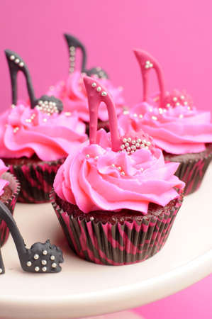 Female high heel shoes decorated pink and black red velvet cupcakes with high heel shoes for teenage, female birthday, or wedding bridal shower - close up on pink cupcake. photo