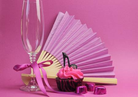 stilleto: Pink party cupcake with black stilleto high heel shoe with champagne glass, fan and chocolates for teenage birthday mothers day christmas bridal shower party table decorations. Stock Photo