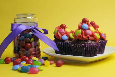 childrens food: Bright colored candy cupcakes for children birthday, Halloween or Christmas party against a cheerful yellow background, with glass candy jar full of sweets.
