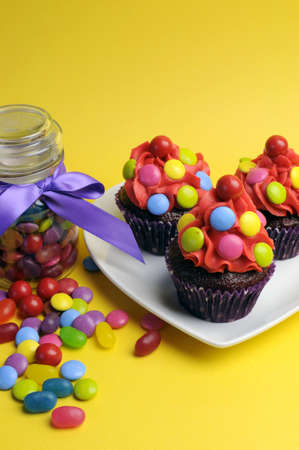 Bright colored candy cupcakes for children birthday, Halloween or Christmas party against a cheerful yellow background, with glass candy jar full of sweets. Vertical. photo