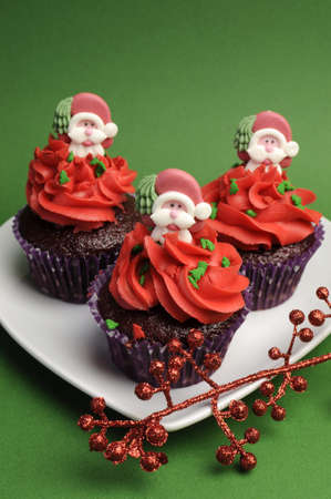 Three Christmas Cupcakes in purple polka dot wrapper with red frosting and santa decoration against a festive green background - vertical. photo
