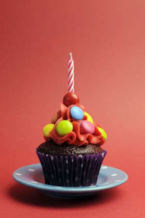 Candy covered chocolate cupcake with red frosting and candy and one birthday candle on red background for Childrens birthday party - with copy space. photo