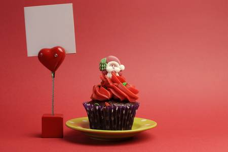 Red Santa Christmas festive cupcake in purple polka dot wrapper on green plate against a red background with red heart table placecard sign with blank message and copy space for your text here. photo