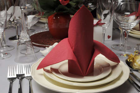 bishop: Red and white theme wedding breakfast dining table setting with red table napkins in bishop style folds, for weddings or Valentine day banquet meal  Close up