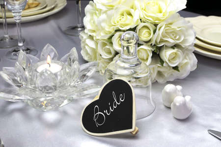 Close up of detail on wedding breakfast dining table setting with a heart shape blackboard place card for Bride setting, and glass bell  photo