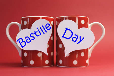 fourteenth: Share a cup of coffee for France National holiday calendar, 14 July, Fourteenth of July, Bastille Day, with two red polka dot coffee mugs and white heart tags with Bastille Day greeting against a red background  Stock Photo