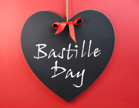 fourteenth: France National holiday, 14 July, Fourteenth of July, Bastille Day, sign or greeting on a heart shape blackboard against a red background Stock Photo