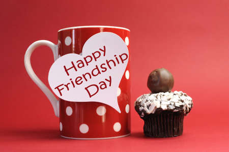friendship day: Celebrate International Friendship Day with a coffee mug, chocolate cupcake mini muffin, and Happy greeting on a white heart tag, against a red background  Stock Photo