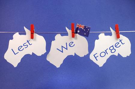 Celebrate Remembrance, November 11, or Anzac Day, April 25,  public holiday with a bright and vivid pegs on a line message greeting across three white Australian maps with an Aussie flag  Stock Photo