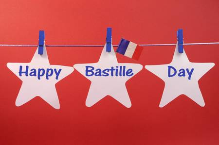 14th: Happy Bastille Day written across white stars hanging from pegs on a line, with French flag, for France public holiday on 14 July