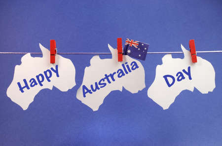 Celebrate Australia Day holiday on January 26 with a Happy Australia Day message greeting written across white Australian maps and flag hanging pegs on a line against a blue background  Stock Photo