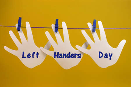 left hand: Left Handers Day message greeting across left hand silhouette cards hanging from pegs on a line against a yellow background, for International Left-handers Day on August 13