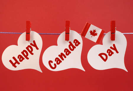 canada day: Happy Canada Day message greeting with the Canadian maple leaf flag hanging from pegs on a line against a red background, for July 1 holiday