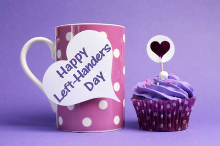 Happy Left Handers Day message written on white heart shape tag on pink polka dot mug with purple cupcake on purple background, for International Left-Handers Day celebrated on August 13