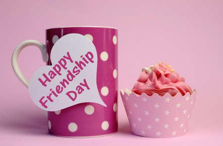 afternoon cafe: Amistad texto del mensaje Feliz Día escrito en signo tag corazón blanco en rosa taza de lunares con la magdalena rosa para el Día Internacional de la Amistad se celebra el 4 de agosto Foto de archivo