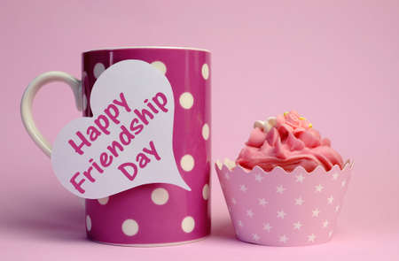 Happy Friendship Day message text written on white heart tag sign on pink polka dot cup with pink cupcake for International Friendship Day celebrated on August 4