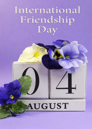 friendship day: Save the Date white block calendar for August 4, International Friendship Day, decorated with blue and white pansy violas on blue purple background