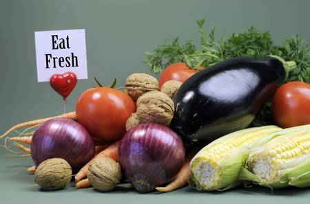Eat Fresh message sign with fresh raw vegetarain food including eggplant, onion, corn, tomatoes, walnut nuts and carrots against a green background for World Vegetarian Day or healthy diet concept  Stock Photo