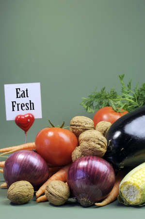 Eat Fresh message sign with fresh raw vegetarain food including eggplant, onion, corn, tomatoes, walnut nuts and carrots against a green background for World diet concept