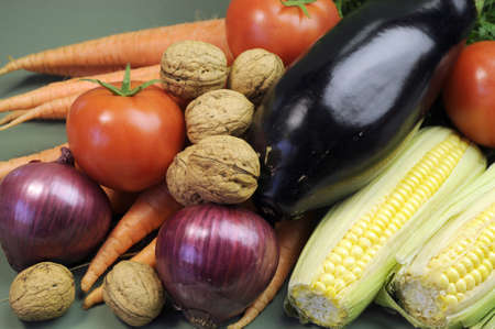 naturopath: Fresh raw food including eggplant, mulnuts nuts carrots tomotoes and corn for healthy diet concept or World vegetarian Day on October 1