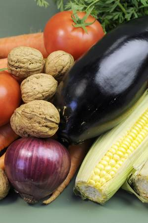 naturopath: Fresh raw food including eggplant, mulnuts nuts carrots tomotoes and corn for healthy diet concept or World vegetarian Day on October 1  Vertical close up