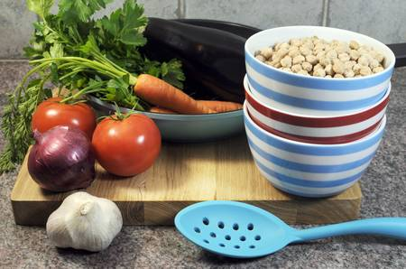 naturopath: Vegetarian cooking concept with eggplant, carrots, tomatoes, and red onion with dried chick peas and blue, red and white cooking utensils for healthy diet concept or World Vegetarian Day on October 1