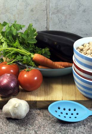 naturopath: Vegetarian cooking concept with eggplant, carrots, tomatoes, and red onion with dried chick peas and blue, red and white cooking utensils for healthy diet concept or World Vegetarian Day on October 1  Vertical  Stock Photo