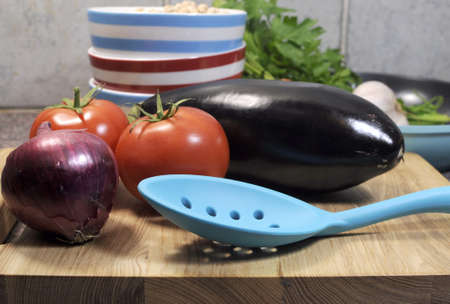 Vegetarian cooking concept with eggplant, carrots, tomatoes, and red onion with dried chick peas and blue, red and white cooking utensils for healthy diet concept or World Vegetarian Day on October 1  Close up  photo