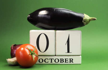 Save the date white block calendar for October 1, World Vegetarian Day with eggplant, tomato and onion on green background  photo