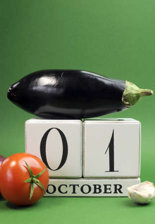 Save the date white block calendar for October 1, World Vegetarian Day with eggplant, tomato and onion on green background  Vertical with copy space  photo