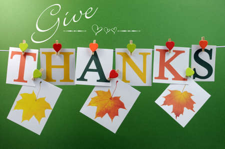 nov: Give Thanks message spelling in letters hanging from pegs on a line for Thanksgiving greeting in autumn colors, with autumn fall leaves