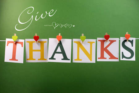 Give Thanks message spelling in letters hanging from pegs on a line for Thanksgiving greeting in autumn colors  Stock Photo