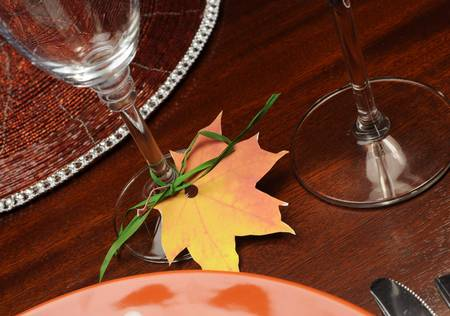 Beautiful Autumn Fall theme Thanksgiving dinner table place setting with Happy Thanksgiving tag attached to silverware  Close up on Fall Leaf glass place holder  photo
