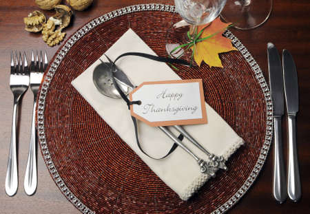 Beautiful Autumn Fall theme Thanksgiving dinner table place setting with Happy Thanksgiving tag attached to silverware  Aerial view with walnuts