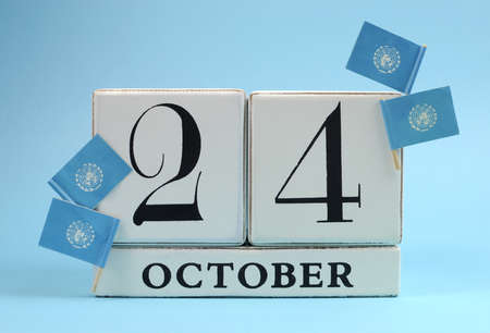 calendario octubre: Guarde el bloque blanco calendario fecha para el 24 de octubre, Día de las Naciones Unidas, con las banderas azules cielo de las Naciones Unidas, contra un fondo de cielo azul Foto de archivo