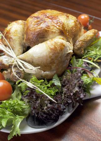 Platter of delicious roast chicken turkey with salad greens and red tomatoes on the vine for a succulent, delicious Christmas or Thanksgiving lunch or dinner meal  Vertical  photo