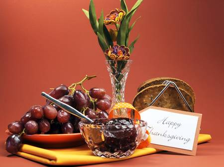 Happy Thanksgiving day break or morning brunch with toast, jelly and grapes against a red brown autumn setting with flowers  photo