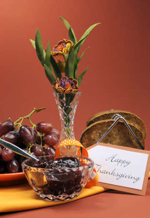 Happy Thanksgiving day breakfast or morning brunch with toast, jelly and grapes against a red brown autumn setting with flowers  Vertical, Stock Photo - 21723952