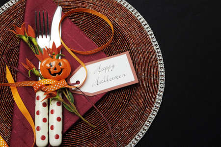 Happy Halloween table place setting with red polka dot cutlery and pumpkin decorations  photo