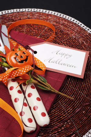 Happy Halloween table place setting with red polka dot cutlery and pumpkin decorations  Close up  photo