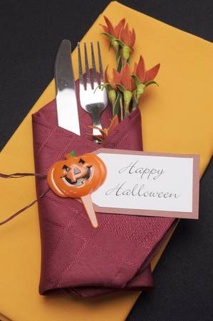 Happy Halloween table place setting with red and orange napkins on a black tablecloth, and halloween decorations  Aerial  photo